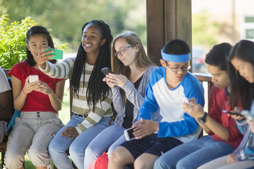 A multi-ethnic group of high school age students are taking selfies with their cell phone cameras together before class.